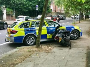 Police car resting against moped