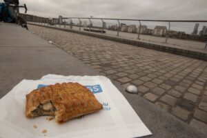 A Gregg's festive bake sat on the paper bag it came in. It is placed on a grey stone bench with the river Thames and an overcast sky in the background