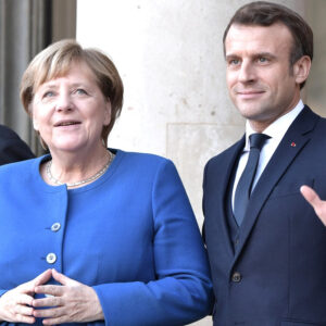 Emmanuel Macron wearing a dark navy suit standing to the right of the frame facing the camera. Next to him on the left of the image is German Chancellor Angela Merkel