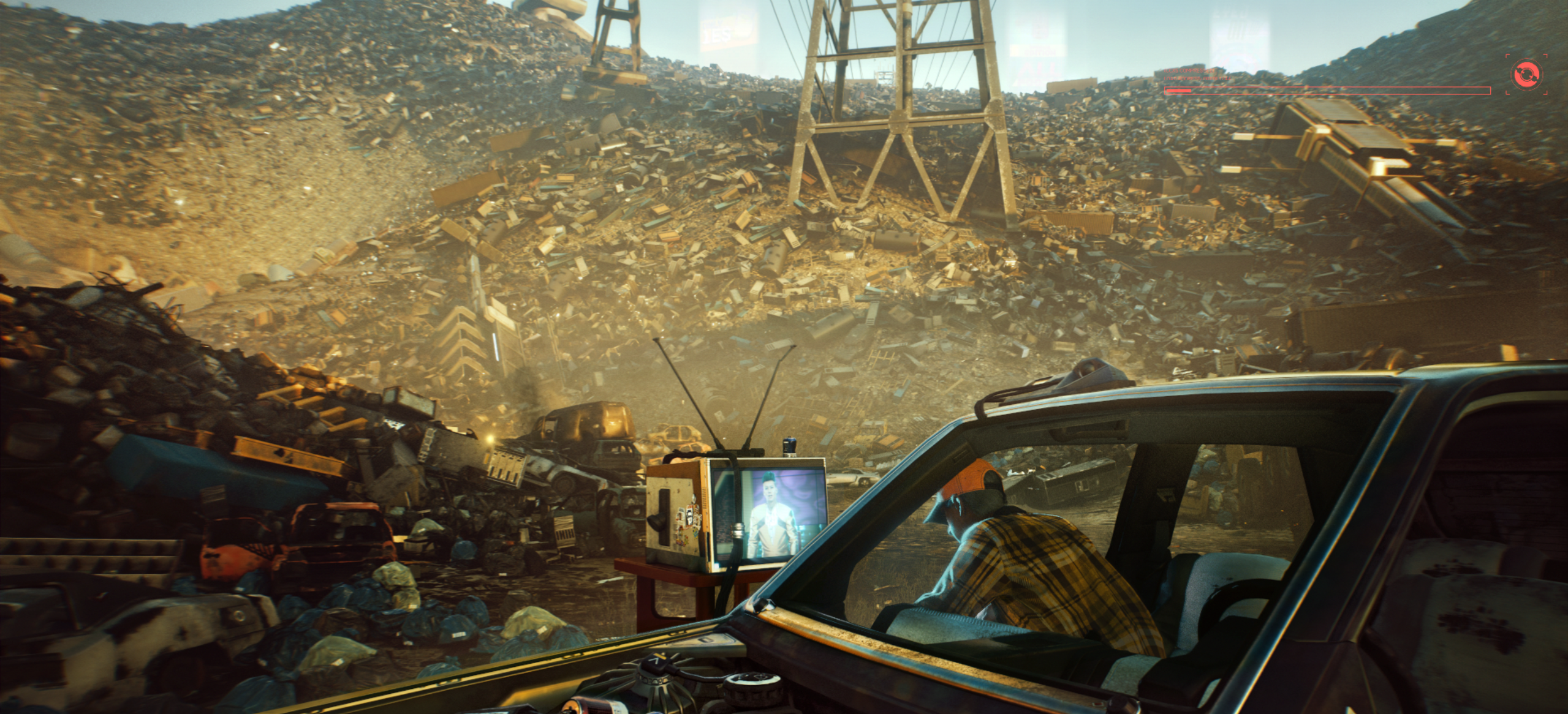 Screenshot of the game Cyberpunk 2077.A man in a yellow plaid shirt and orange cap faces away from the camera watching a TV in a scrap yard. The old frame of a car sits in the foreground.