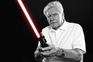 Dave Prowse, actor of Star Wars' Darth Vader, holding a lightsaber.