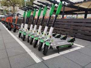 A row of white and green Lime scooters, followed by a more distant row of orange and black scooters in a scooter parking spot marked by a white painted line. In the background is a wooden fence and large outdoor umbrellas.