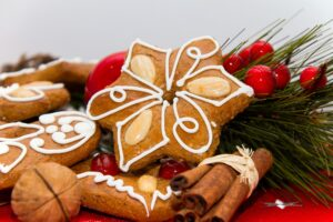 Gingebread cookies arranged on a red tablecloth with holly and cinnamon sticks